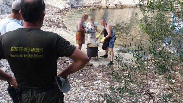 Agentes de Medio Ambiente en Cala Figuera paralizando un grupo de personas que intentaba cocinar