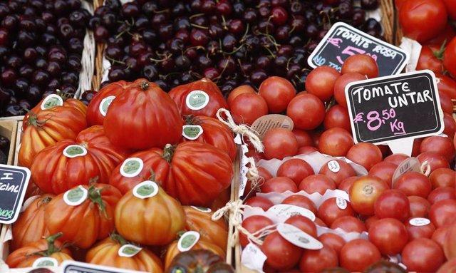 Tomates e cereixas nun mercado.
