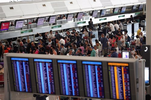 Pasajeros intentando hacer el check-in en el Aeropuerto Internacional de Hong Kong