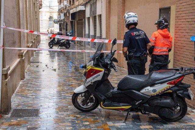 Bomberos retiran cascotes caídos de un edificio en la calle Bodegones de Cartagena