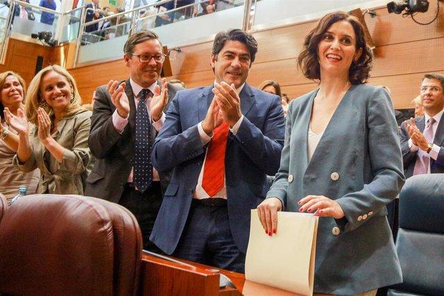La candidata del PP a la Presidencia de la Comunidad, Isabel Díaz Ayuso (1d), recibe el aplauso de la bancada del Partido Popular en la Asamblea de Madrid, tras su discurso en  la primera sesión del segundo pleno de su investidura.