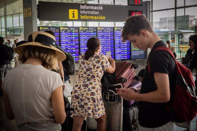 Diferents viatgers esperanfrente al panell d'informació dels vols de Sortida de l'Aeroport 'Josep Tarradellas Barcelona-El Prat', durant la vaga del personal de terra d'Iberia a Barcelona al juliol.