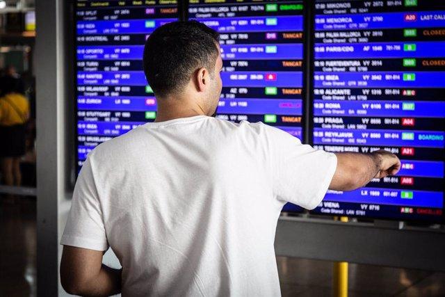 Un home mira el panell d'informació dels vols de Sortida de l'Aeroport  'Josep Tarradellas Barcelona-El Prat', durant la Vaga del personal de terra d'Iberia a Barcelona.