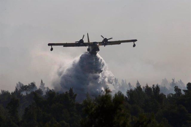 Un avión dscarga agua sobre el bosque en llamas en Eubea