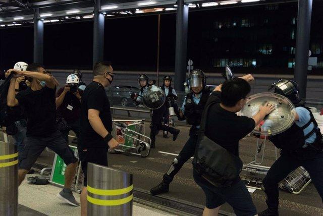 Enfrentamiento entre manifestantes y policías en el aeropuerto de Hong Kong