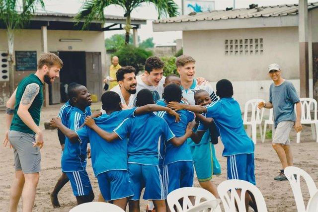 Jugadores del AE Ramass jugando con niños en uno de sus viajes.