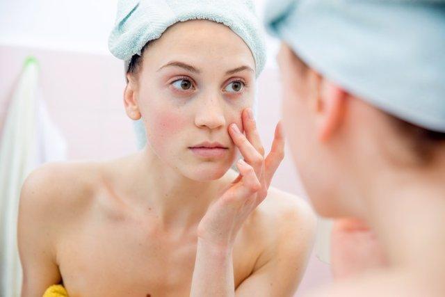 Mujer en el baño observando sus ojeras.