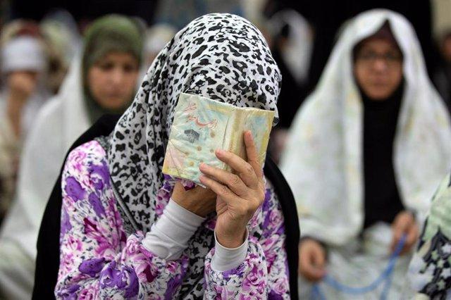 Mujer rejando tamándose con el Corán