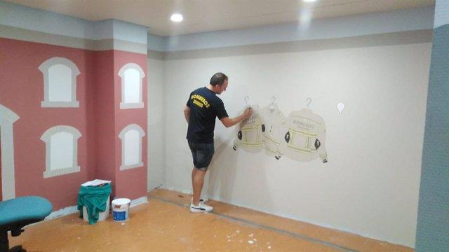 Un bombero decora una sala de espera del Hospital Infantil
