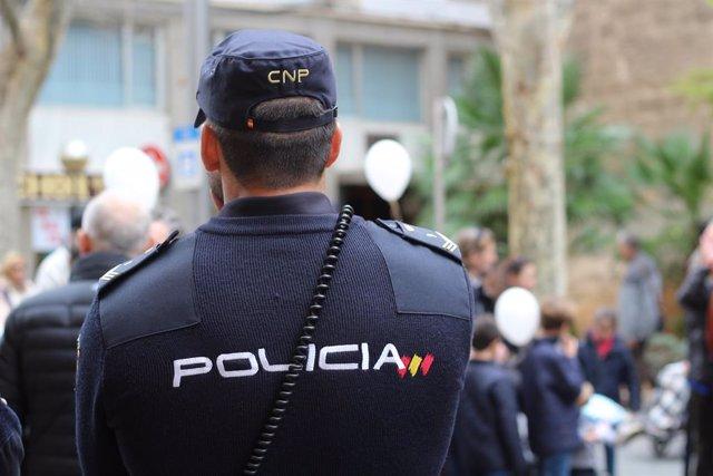 Un agent de la Policia Nacional, d'esquena.