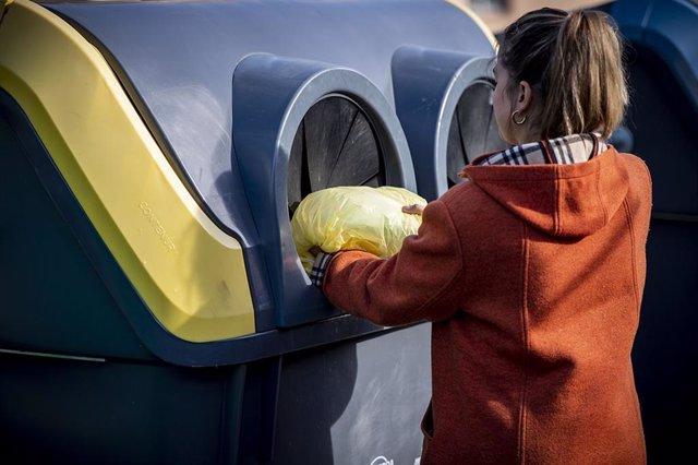 Una ciudadana deposita residuos en un contenedor