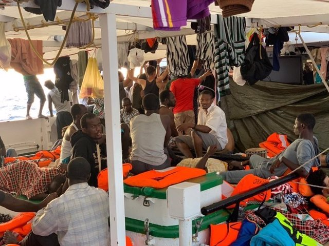 Personas rescatadas por el Open Arms, fondeado frente a la isla italiana de Lampedusa.