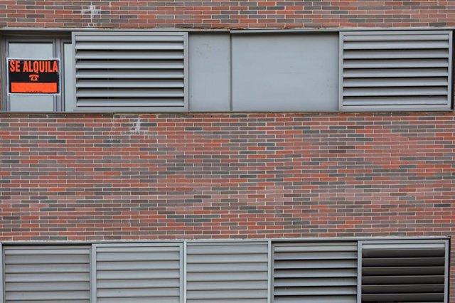 En la ventana de un piso se ve colgado un cartel en el que se lee 'Se alquila'.
