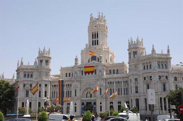 Varias banderas de España en las inmediaciones del Palacio de Cibeles, sede del Ayuntamiento de Madrid, donde propiamente ondean dos banderas de España (una de gran tamaño impuesta por Vox) y la bandera LGTBI en la parte izquierda del edificio.