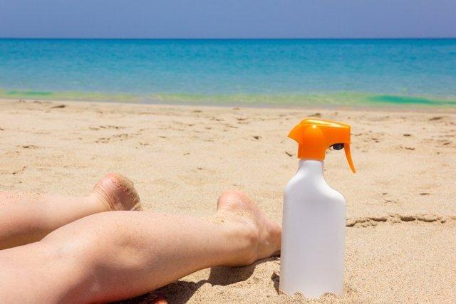 Piernas de mujer boca abajo sobre la arena en la playa, botella de spray de loción solar