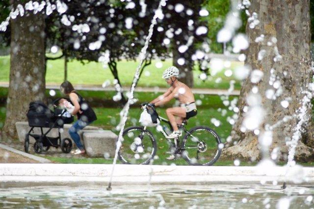 Una fuente y personas en un parque en verano.