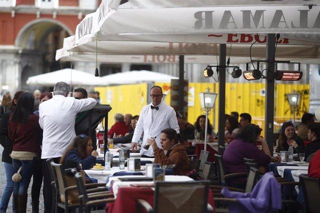 Camareros trabajando en las terrazas de un local.