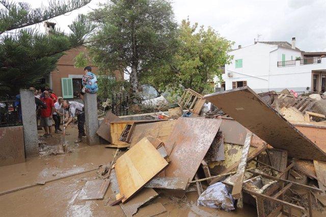 Una familia achica agua en su casa tras la torrentada de Sant Llorenç