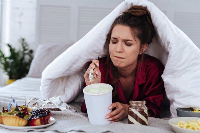 Mujer comiendo con ansiedad en la cama.