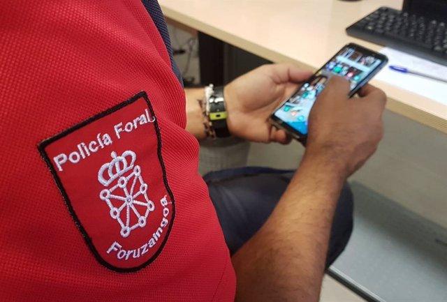 Un agente de la Policía Foral investiga un teléfono móvil