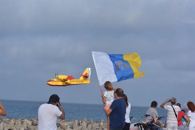 Un grupo de vecinos de Gran Canaria, toman fotos de uno de los hidroaviones que trabajan en las labores de extinción del incendio de la isla.