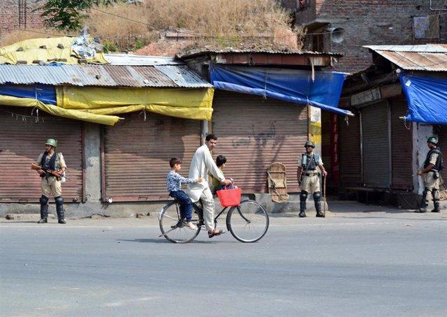 Un hombre pasea en bicicleta frente a miembros de las fuerzas de seguridad en Cachemira