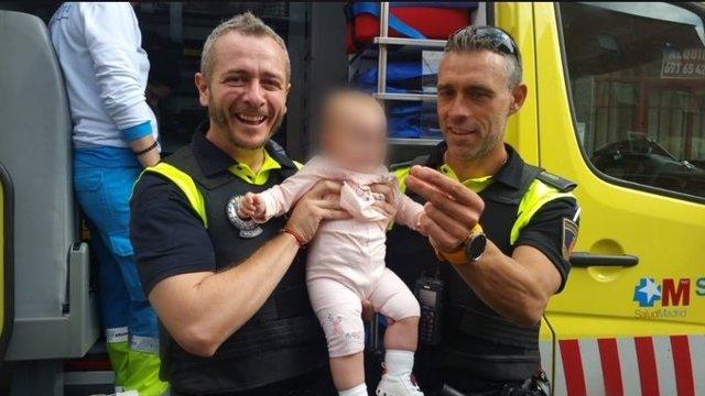 Agentes de Emergencias 112 Comunidad de Madrid posan junto a una bebé de ocho meses que ha sido auxiliada mientras se asfixiaba con un plástico que se había tragado.