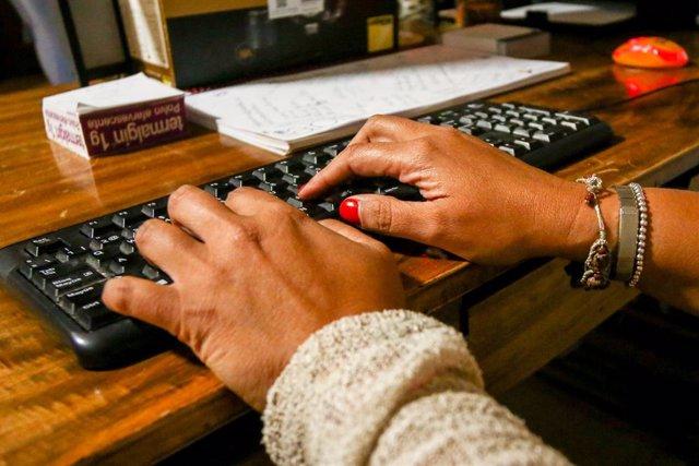 Unes mans de dona escriuen en el teclat d'un ordinador, sobre una taula de fusta.