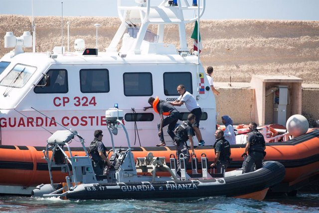 "20 August 2019, Italy, Lampedusa: Gurdia vaig donar Finana officials transport a migrant to the port of Lampedusa from the ship ""Open Arms"" of aid organisation Proactiva Open Arms. Migrants llauri jumping out of desperation from the rescue boat, stran"