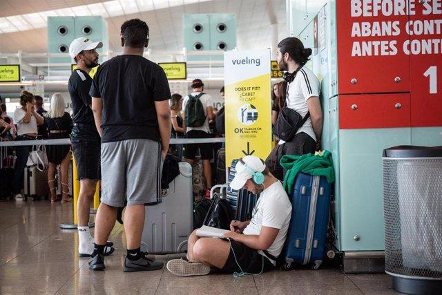 Diferentes viajeros esperan junto al puesto de Check-In de la compañía Vueling en el Aeropuerto 'Josep Tarradellas Barcelona-El Prat', durante la Huelga del personal de tierra de Iberia en Barcelona en julio.