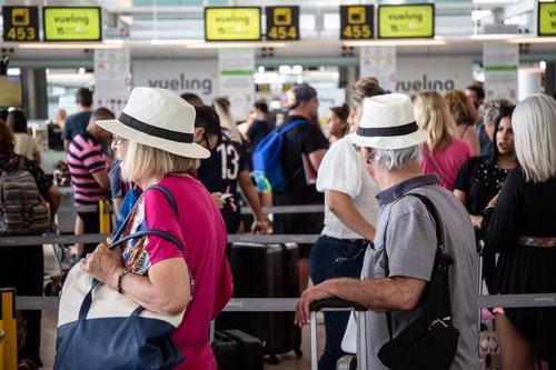 Diferentes viajeros esperan en el puesto de Check-In de la compañía Vueling en el Aeropuerto 'Josep Tarradellas Barcelona-El Prat', durante la huelga del personal de tierra de Iberia en Barcelona durante el mes de julio.