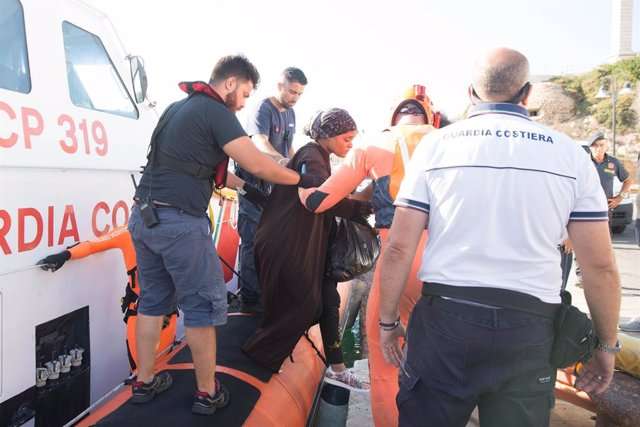 """20 August 2019, Italy, Lampedusa: A woman evacuated by the Guàrdia Costeria for a medical emergency at the port of Lampedusa from the ship """"Open Arms"""" of aid organisation Proactiva Open Arms. Migrants llauri jumping out of desperation from the rescue boat"""