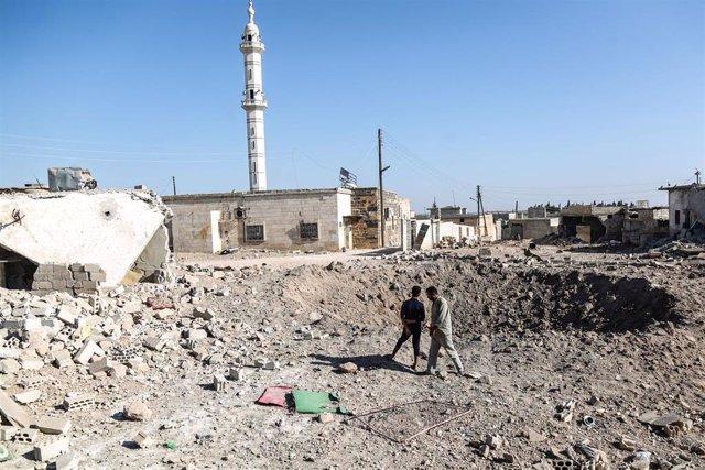 Personas junto al cráter dejado por un bombardeo aéreo en Idlib