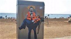 L'artista urbà Tvboy pinta Camps d'Open Arms com un sant a la Barceloneta (EUROPA PRESS)