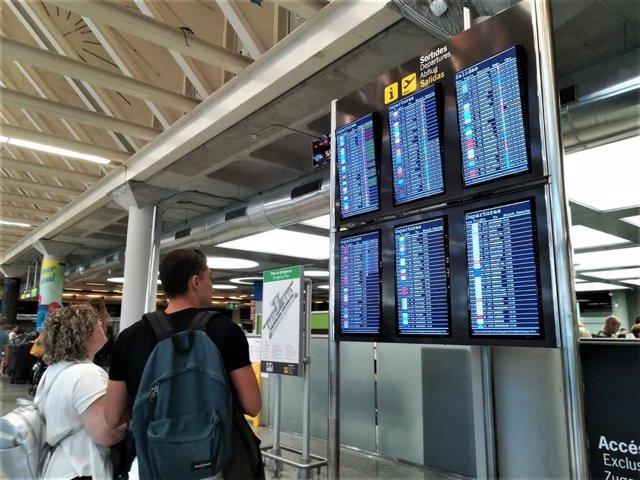 Turistas comprueban la información de las pantallas de embarque en el aeropuerto de Palma.