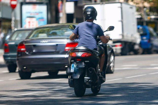 Un home circula en la seva moto per un carrer al costat d'altres vehicles.