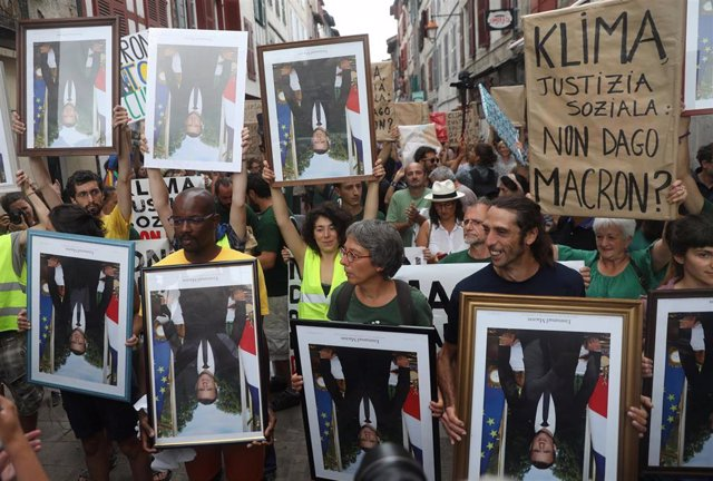 Activists march with stolen portraits of French President Emmanuel Macron during the G7 summit