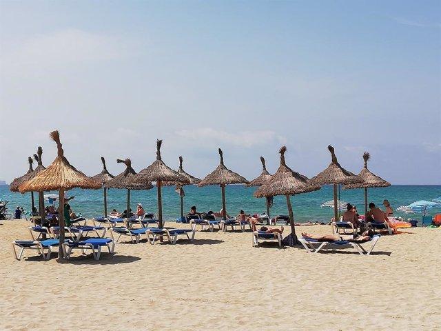 Turistas en hamacas bajo las sombrillas de la Playa de Palma.