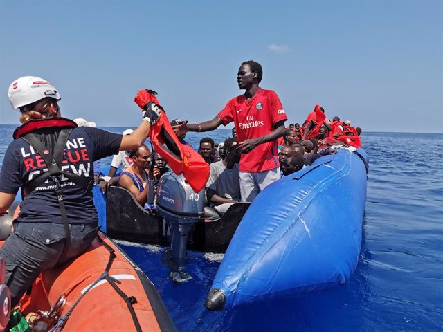 "26 August 2019, Libya, --: A rescue crew member gives a life jacket to an African migrant after he and more than hundreds other migrants were rescued by the German aid ship ""Eleonore"" at the Mediterranean Sea. Photo: Johannes Filous/dpa"