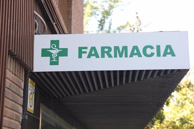 Letrero verde de una farmacia en una calle de Madrid.