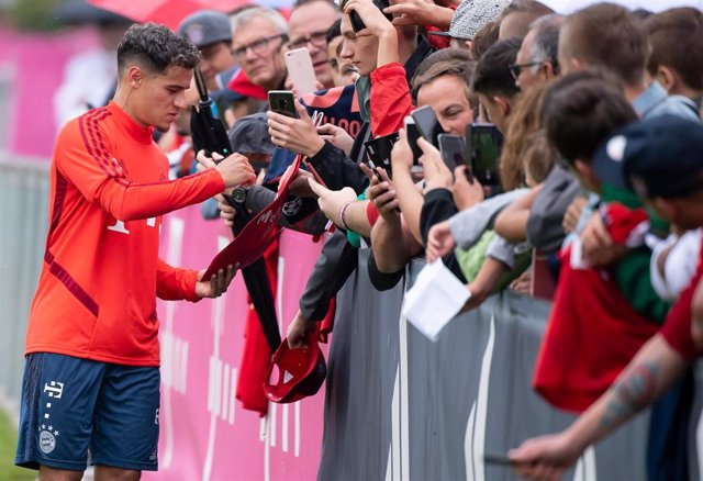 20 August 2019, Bavaria, Munich: Brazilian footballer Philippe Coutinho (L) writes autographs after his first public training session after joining FC Bayern Munich. Photo: Sven Hoppe/dpa - IMPORTANT NOTICE: DFL and DFB regulations prohibit any use of pho