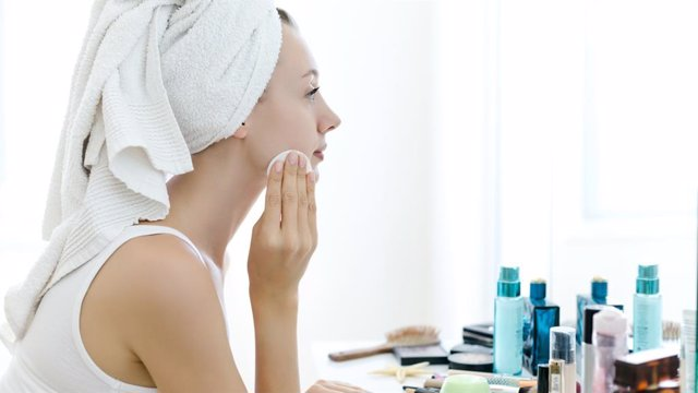 Mujer retirándose el maquillaje y dándose crema ante el espejo.