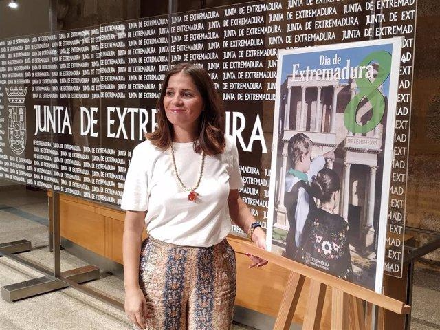Isabel Gil Rosiña, posa junto al cartel del Día de Extremadura
