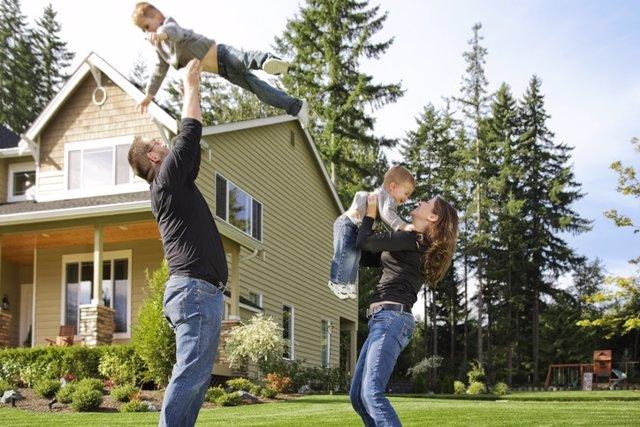 Familia jugando con sus hijos; niños felices. Casa, barrio
