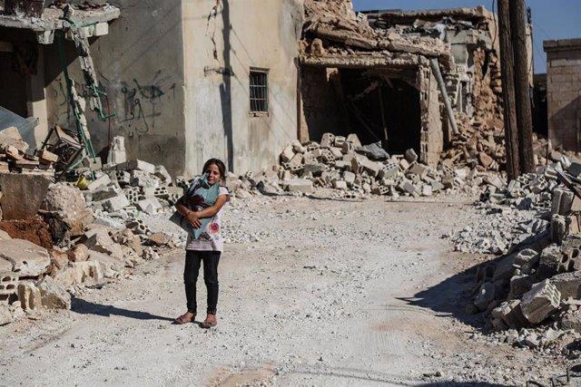 Una niña junto a edificios bombardeados en Idlib