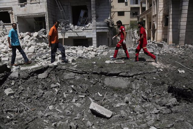 Personas junto al lugar de una explosión en Idlib