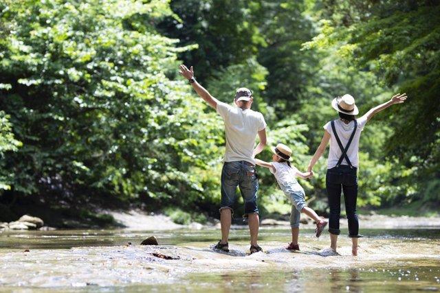 Familia de vacaciones feliz de excursión en un río.