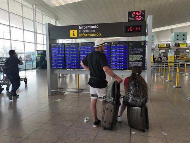 Pasajeros en el Aeropuerto de Barcelona ante un panel de información.