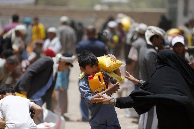 Un niño carga comida y bebida recibida de una organización benéfica local en Sanaa, Yemen. 5 junio de 2016 REUTERS/Khaled Abdullah