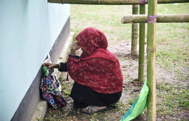 Una mujer busca su nombre en una lista del registro civil de Assam